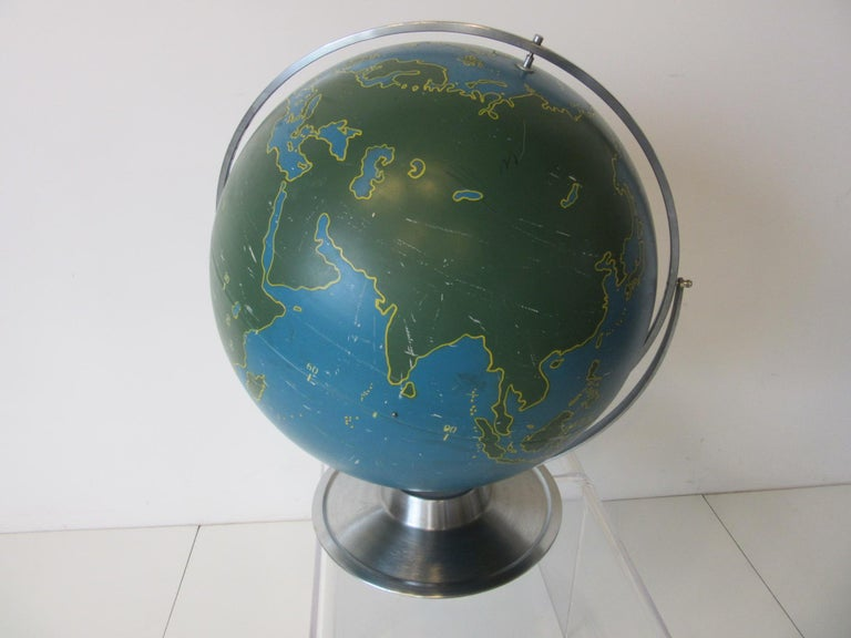 A metal rotating globe with painted countries, bodies of water, latitude and longitude numbers used for aviation and military navigational training with brushed stainless steel base and ring. This large very well crafted hollow globe is the tops for