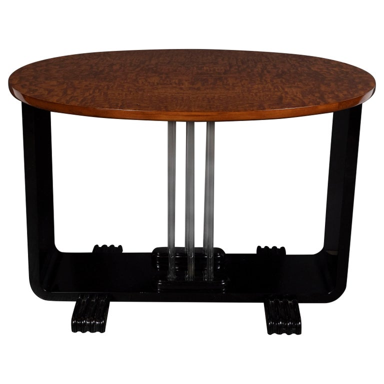 This refined Machine Age Art Deco side table was realized in the United States, circa 1935. It features an oval burled elm top offering a stunning grain; and a U-Form composed of two black lacquer streamlined supports that sit on reeded streamlined