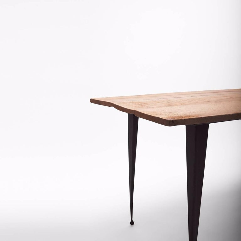 Made to order reclaimed oak top table with tapered black iron legs. This simply designed table can be custom made in any size and leg height. The legs are custom made in wrought iron. Top is made of 8