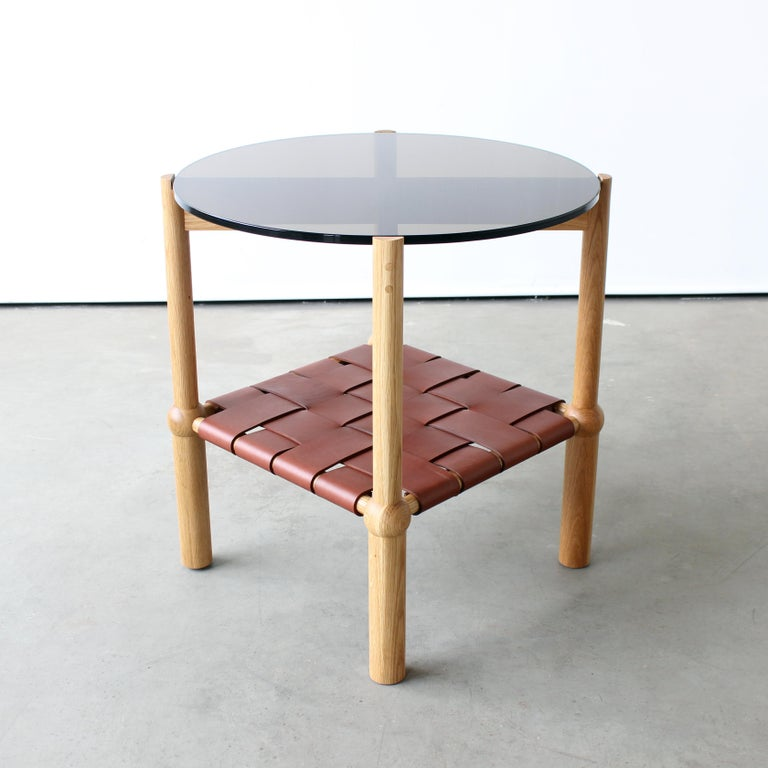 """Mae side table  by Crump and Kwash   Solid wood frame / hand-turned legs / zero voc oil finish / woven veg tanned leather / 1/2 in circular glass top   Dimensions: 24"""" W x 24"""" D x 24"""" H  Wood: Walnut, white oak, maple, blackened oak"""