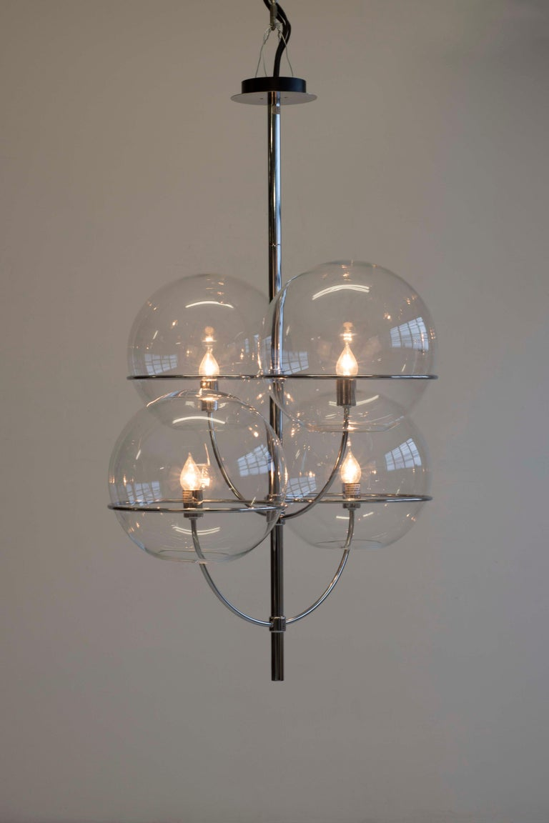 Lyndon by Vico Magistretti for Oluce; chrome-plated finished candelabra-style body, enclose transparent glass spheres, inside which the light bulb is hosted.