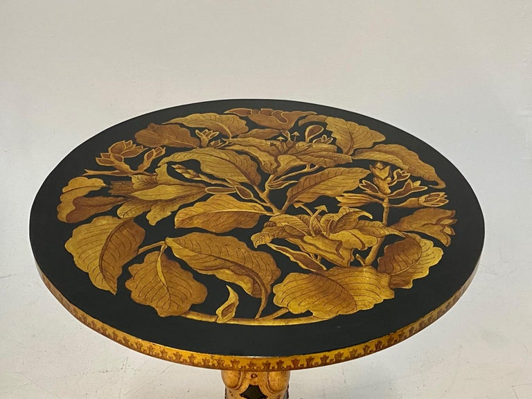 Sublimely decorated hand carved and painted round side or end table with striking black and gold color combination, having 4 curved feet, raised gilt decoration on column and feet, and gorgeous leaf motife embellishments. Original label underside.