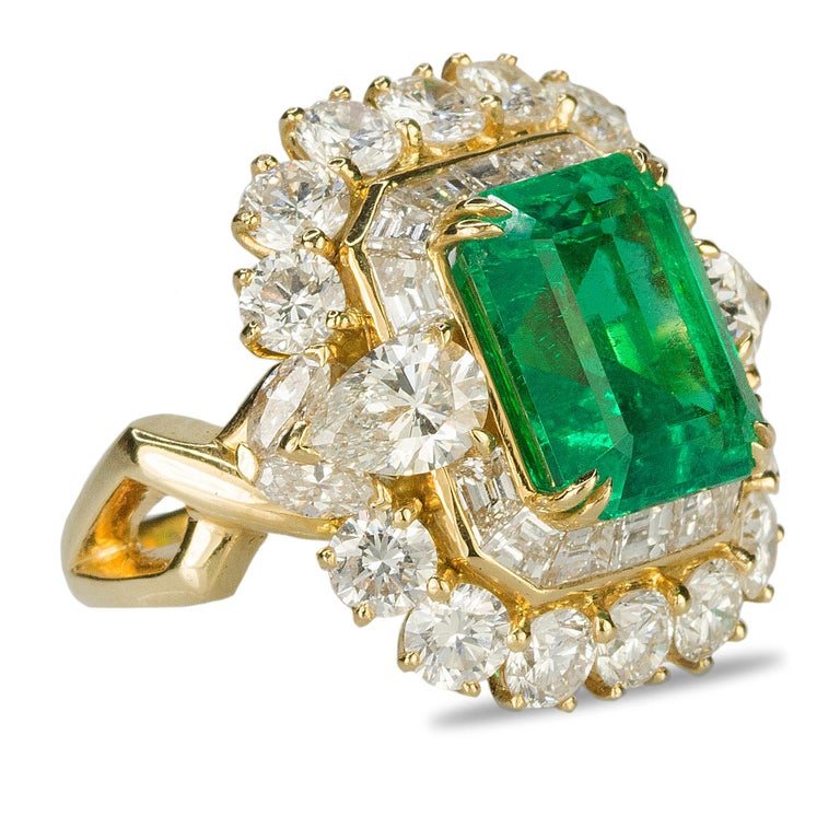 18k ring containing one AGL certified fine 6.25 carat Colombian Emerald and and 2 pear shape diamonds, 14 round brilliants and 14 baguette diamonds with a total weight of approximately 5.60