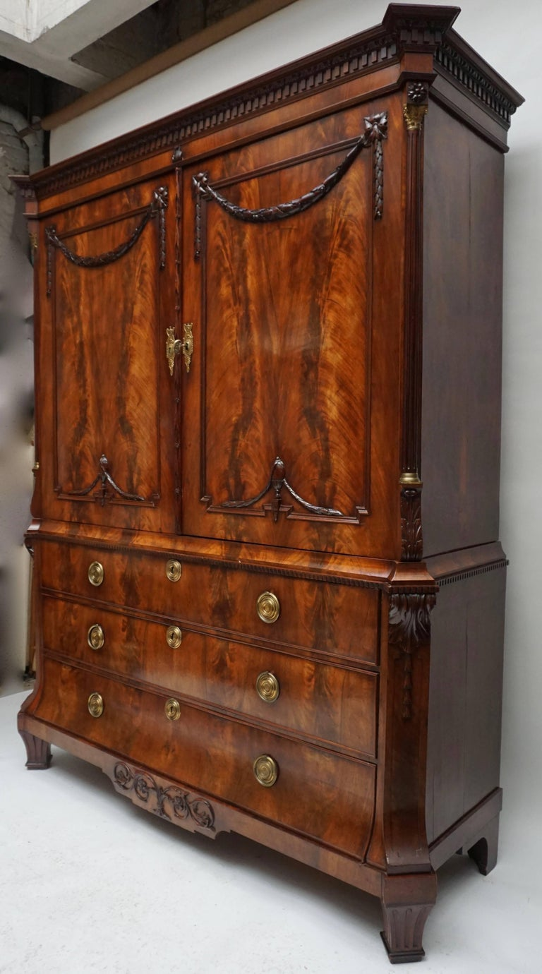A magnificent mahogany neoclassical Dutch cabinet, the underpart with three graduated drawers under a pair of cupboard doors, the whole with chamfered corners with elegant reeded Corinthian columns in the upper part. The doors are decorated with