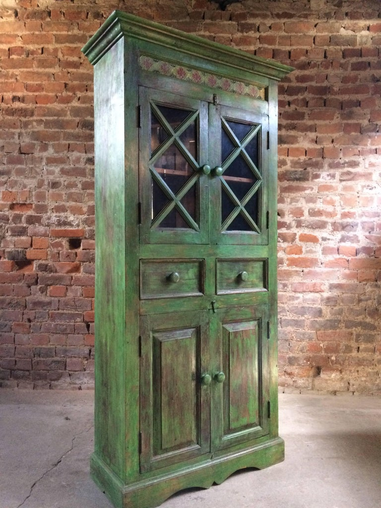 A magnificent early 20th century French painted Teak cabinet, painted in a dark green ground with heavily distressed finish, the corniced top with a tiled decoration over two glazed panelled doors with a single shelf within, over two frieze drawers
