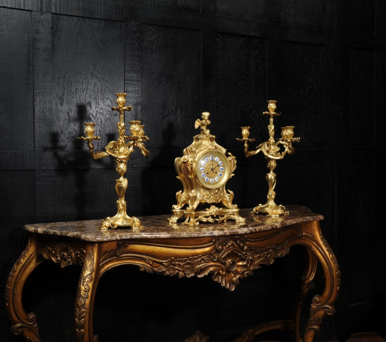 A very large and fine antique French clock set, circa 1880. It is of Rococo design in the manner of Juste Aurele Meissonier and boldly modelled in gilt bronze. Waisted keyhole shape with acanthus leaf shoulders, 'C' scroll feet standing on its