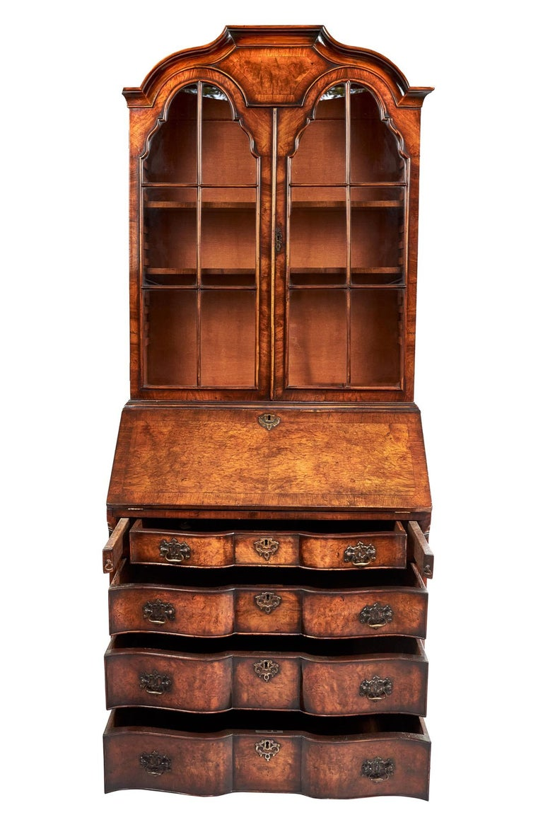 This is an outstanding Queen Anne revival walnut bureau bookcase having an attractive shaped moulded top with a pair of dome topped doors. The pretty cross banded bureau fall opens to reveal a leather inset and a lovely shaped interior with a centre