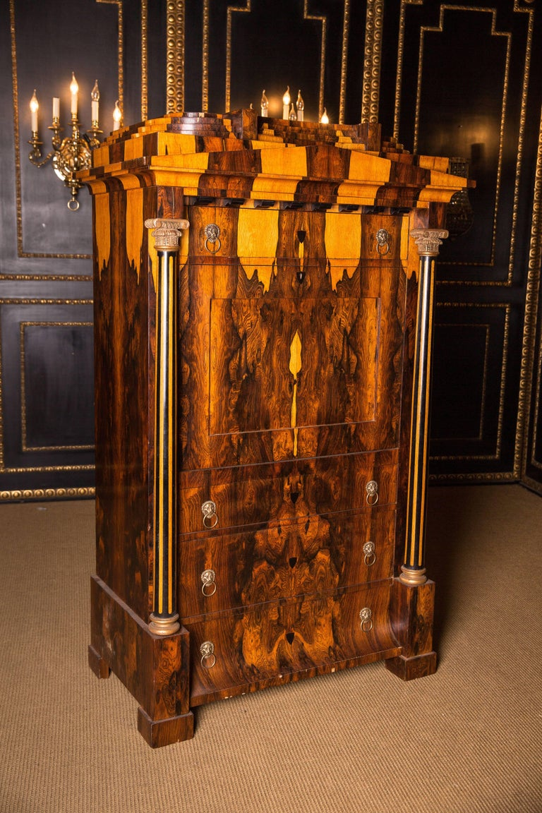 Exotic Indian Palisander on solid conifers. Architecturally arranged front. High-right body on padfoot feet. Fitted with three drawers of different sizes, the base drawer is curved. Straight writing plate, behind staggered office division. Flanked