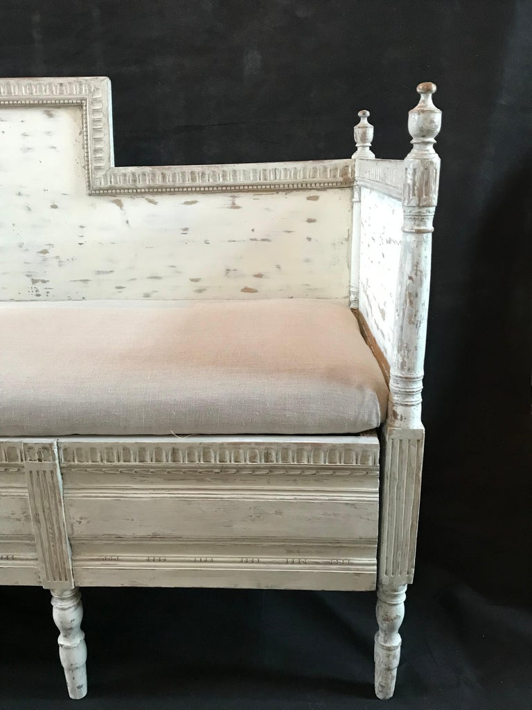 A Swedish Gustavian painted settee or sofa in a gorgeous antiqued grayish white, with classic simple carved wood frame, pretty finials and newly upholstered cushion seat.