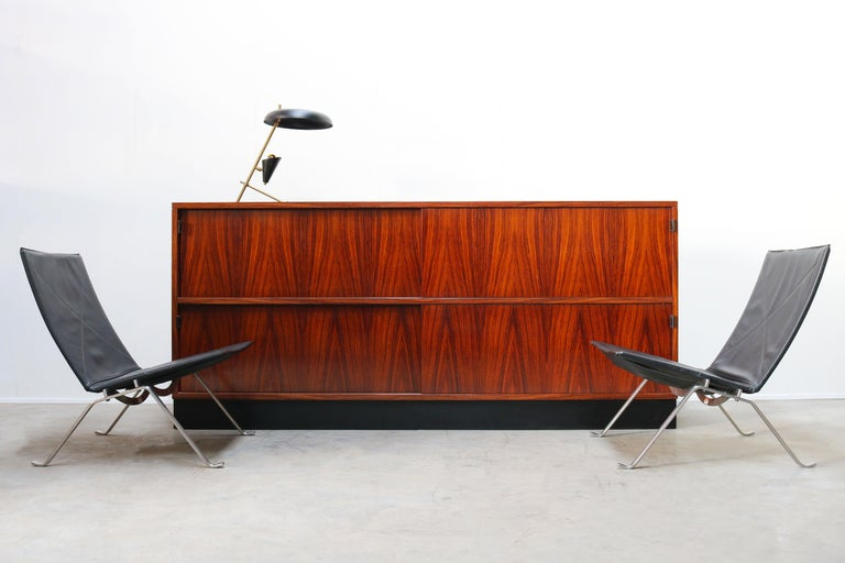 Magnificent large rosewood sideboard by Florence Knoll for Knoll International in the 1950s. The sideboard has 4 sliding doors with black leather grips. Wonderful rosewood grain that looks Royal and warm. The rosewood combines perfectly with the