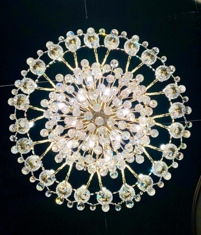 From a mansion estate, this Schonbek Contessa 36 light chandelier with a gold finish metal frame blossoms like a rare flower, with a graceful, hand-formed crystal body and a kaleidoscope of dense crystal ornaments. Chandelier features 24 candle