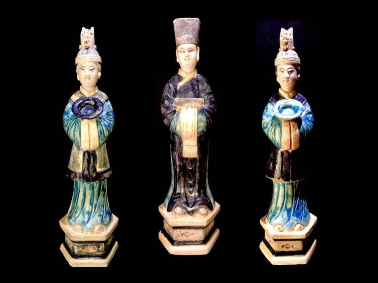 A magnificent set of 3 graceful terracotta figurines from the Ming Dynasty '1368-1644' AD. These elegant courtiers are standing over a high hexagonal plinth and wears fine robes in various blue tones. The unglazed areas have pigmented colors in red,