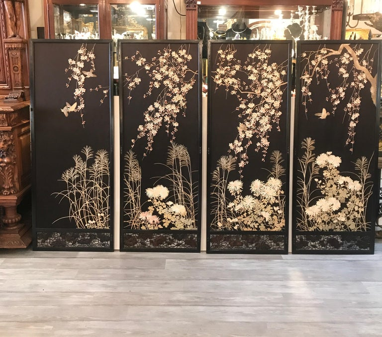 A set of four hand needlework silk panels in black lacquered frames. The panels with a black silk background with embroidered cherry blossoms, birds and spider mum florals. The high quality and expert talent of the needlework done by a Japanese
