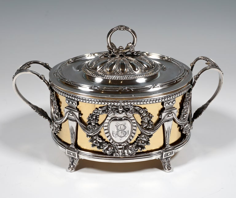 Silver vessel as a breakthrough work on feet, standing on an oval ground plan, richly decorated with wreaths of flowers, monogrammed heart-shaped cartouches, festons and pilasters, openworked raised handles with acanthus decoration, oval lid with