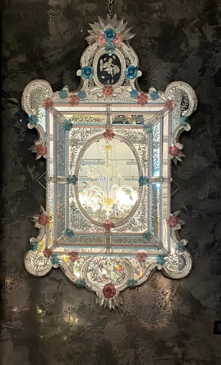 This beautiful Venetian mirror features etched floral motifs adorning the mirrored frame. Along the edges of the frame are glass rope accents and numerous glass pink and blu flowers. Executed by the great a Master of Murano. Excellent condition.