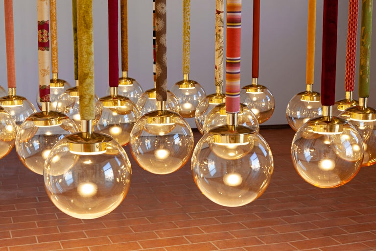 Designed by Filippo Feroldi for Purho and Colleoni Arte, Magus 5 is a chandelier composed of five Murano blown glass spheres of 18 cm each — available in amber color, tobacco or green lagoon — fitted linearly to a rectangular supporting structure
