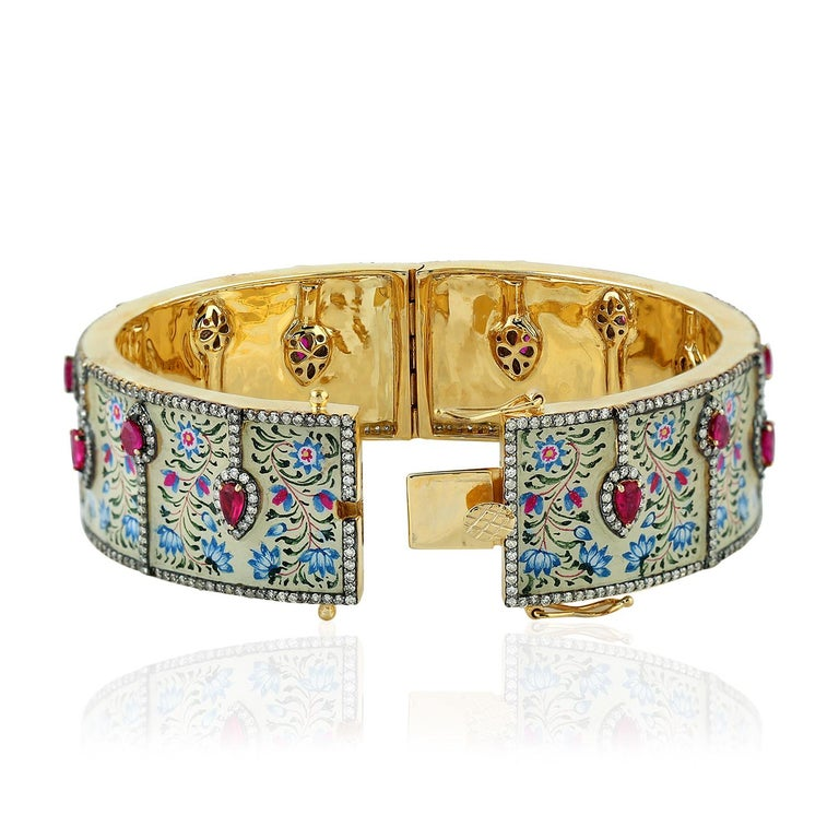 The pieces in Maharaja collection features unique hand painted miniature art set with 18K gold, sterling silver & 4.18 carats diamonds.  This beautiful bangle is filled with bright 2.45 carats of rubies that contrast the enamel art. Clasp