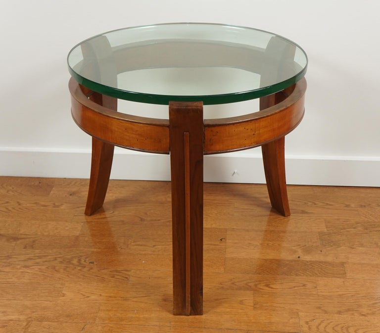 A round occasional table featuring a tripod frame in mahogany with a lowered skirt and three outward bending tapering legs. Also features a very thick glass top.