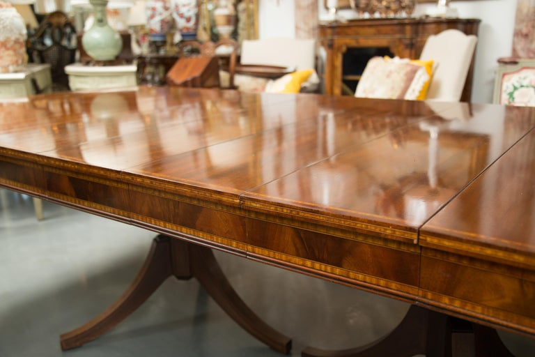 This is a very pleasant inlaid mahogany dining table with four additional leaves for extension. The top has a straight edge and is positioned over a prominent inlaid frieze. The table is supported by two baluster fluted pedestals, terminating each