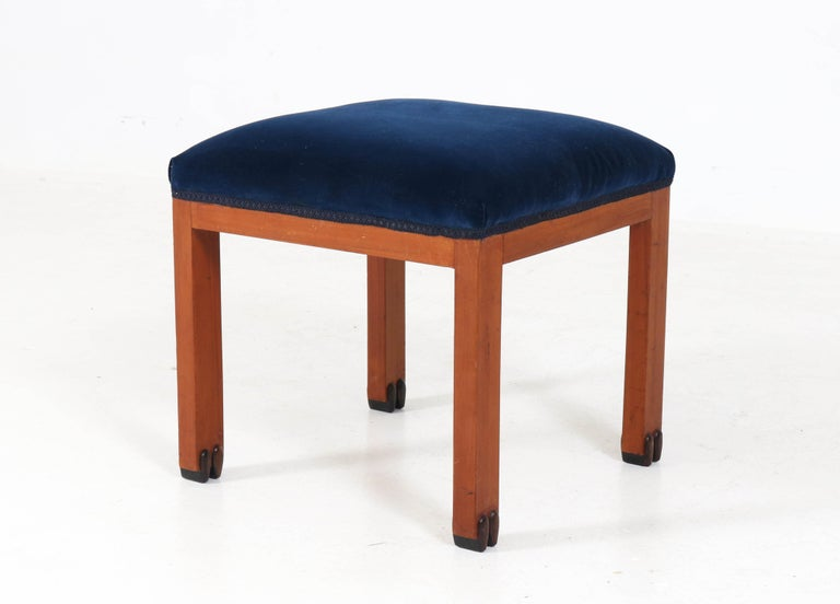 Offered by Amsterdam Modernism: Wonderful Art Deco Amsterdam School stool. Striking Dutch design from the 1920s. Mahogany with new blue upholstery. Solid ebony Macassar details at the legs. In good original condition with minor wear consistent with