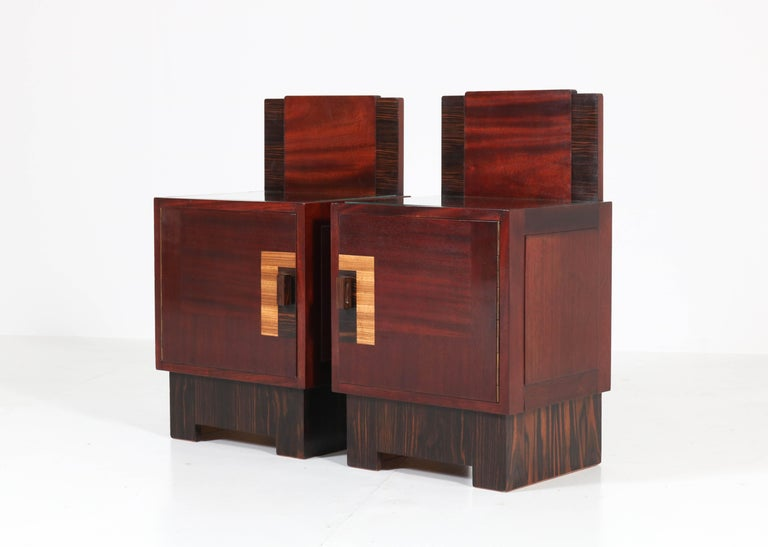 Magnificent and rare pair of Art Deco Haagse School nightstands or bedside tables. Design by 't Woonhuys Amsterdam. Striking Dutch design from the 1920s. Mahogany with Macassar ebony and sycamore veneer and glass tops. This hard to find pair is