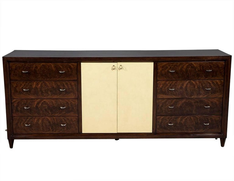 Mahogany Art Deco inspired cabinet buffet. This luxurious Art Deco mahogany cabinet features drawer faces with custom stainless steel ring hardware, accentuated with goatskin finished parchment doors for a luxe, sleek and refined look.