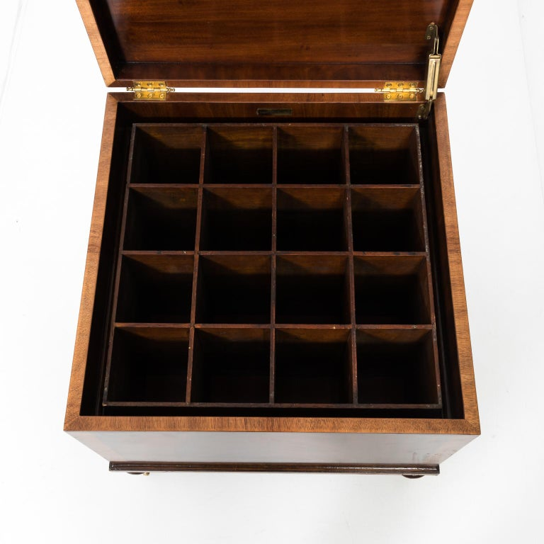 Circa 20th century square cellaret in mahogany by Maitland-Smith with sixteen compartments. The piece also features brass hardware decorated with foliage and castors. A maker's plaque is also found on the inside. Please note of wear consistent with