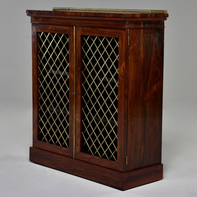 Late 19th century English mahogany chiffonier features an open work brass gallery and two hinged locking doors with brass lattice fronts. Two internal shelves. Unknown maker.   Has 1 key.