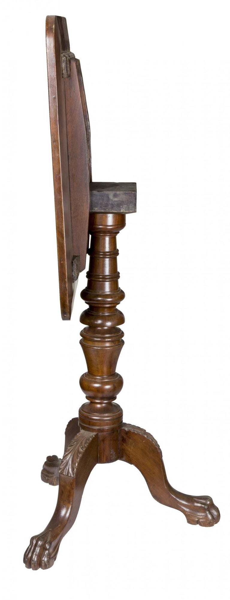 This candle stand exhibits a vigorously turned column supported on three cabriole legs with carved acanthus molding and strong paw feet. It is of heavy, dense mahogany and is robust in its appearance. The top support is interestingly executed with