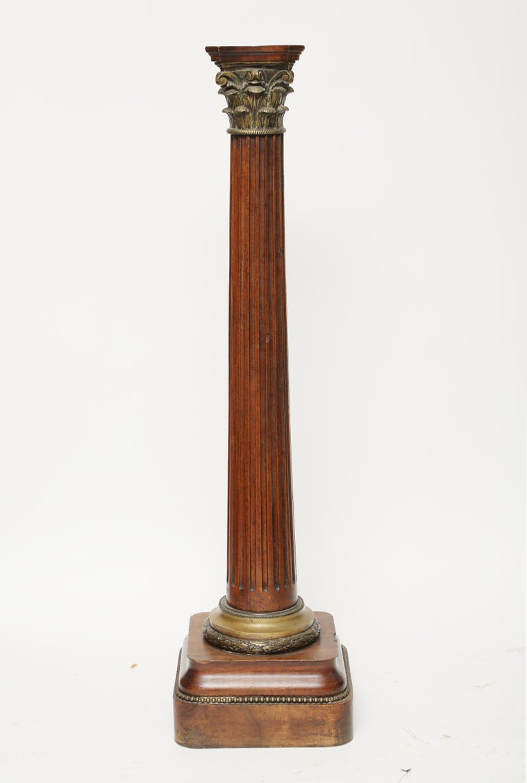 A mahogany fluted column with a gilt brass Corinthian capital. The column terminates with a brass collar of laurel leaves and beaded trim. The round cornered base also has a beaded trim.