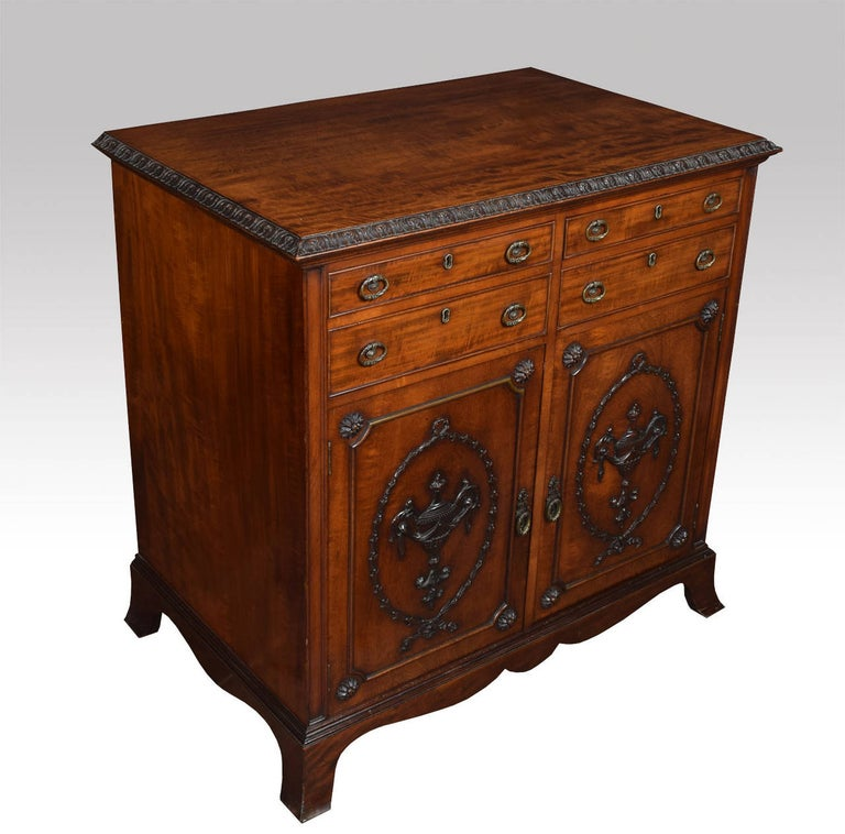 Mahogany commode in the influenced of Robert Adam, the rectangular top having carved edge above four short drawers with tooled brass handles over two doors with classical urns, ribbon and swags mouldings, opening to reveal single fixed shelf Raised