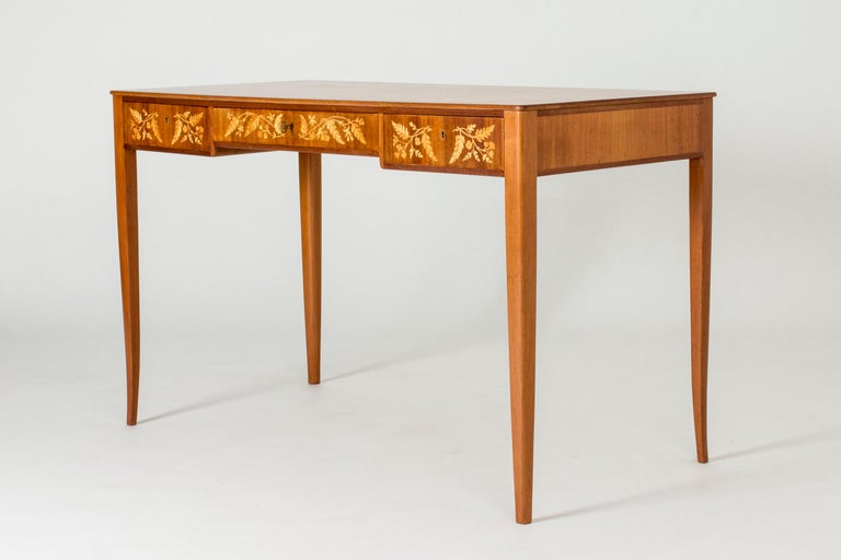 Beautiful small desk by Carl Malmsten, in a light design with slender, subtly curved legs. Lovely inlays of birch in a pattern of flowers and leaves.