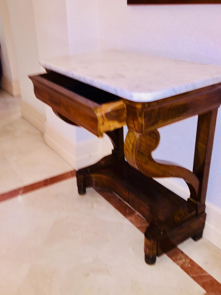 Mahogany Directoire Restauration French marble-top console table. The size makes this piece easy to use in any place. Details, carved Palmettes on the base, lemon tree filets inlayed are interesting and refined. The design of the two legs is