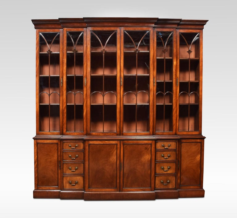 George III style mahogany breakfront bookcase. The molded cornice with carved frieze over two central cupboard doors with arched beaded glass, with stylized floral decoration. Flanked on each side by narrow cupboards and a wider cupboard, fitted