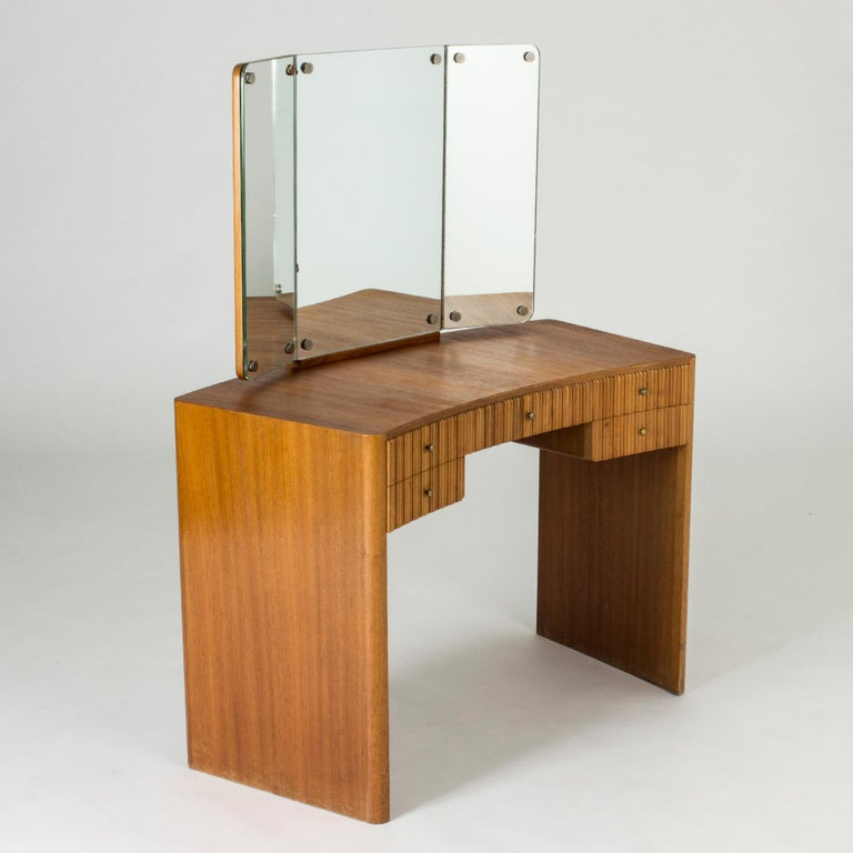 """Beautiful mahogany dressing table by Carl-Axel Acking, with clean rounded lines. Mirror in three sections with adjustable sides. Striking """"corrugated"""" look of the wood on the drawer fronts, neat brass knobs."""