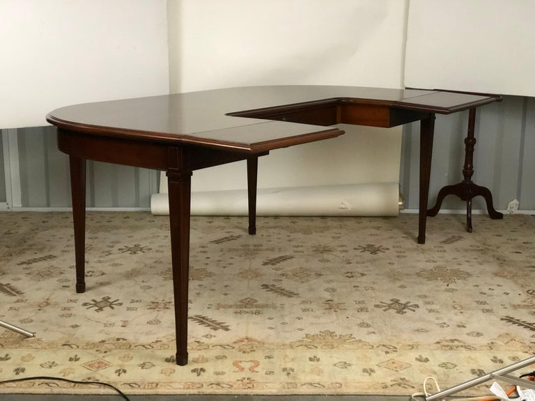 20th century American mahogany demilune shaped desk or writing table with drop-leaf extensions flanking a fitted drawer in the frieze. The table is raised on tapered legs and spade feet. The desk opens to 46.25 inches deep when the leaves are fully