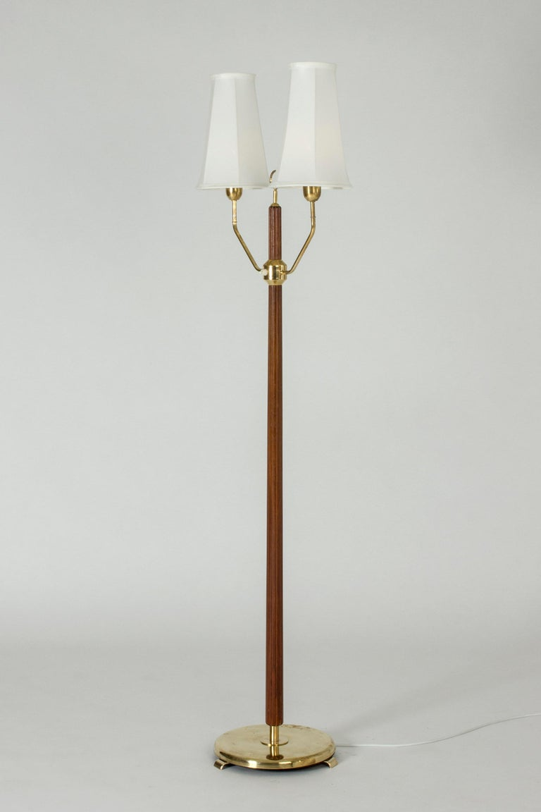 Elegant floor lamp with two shades by Hans Bergström. Made from brass with a mahogany stem embossed with stripes along the length. Decorative hoop detail between the shades.
