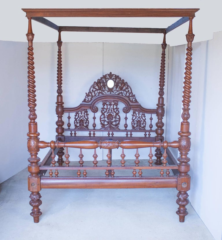 Mahogany four-poster tester bed from British India, circa 1920, with elaborate hand carvings of two winged goddesses, flowers, grapes and shells surrounding an oval mirror on the headboard. The bed's four posts have a beautiful tapered serpentine