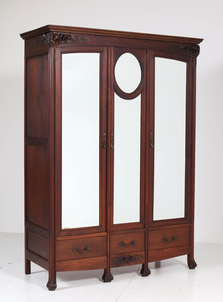 Magnificent Art Nouveau armoire or wardrobe. Striking French design from the 1900s. Solid mahogany with original beveled mirrored glass. handcrafted carving with various flowers. This wonderful piece of furniture can be dismantled for safe