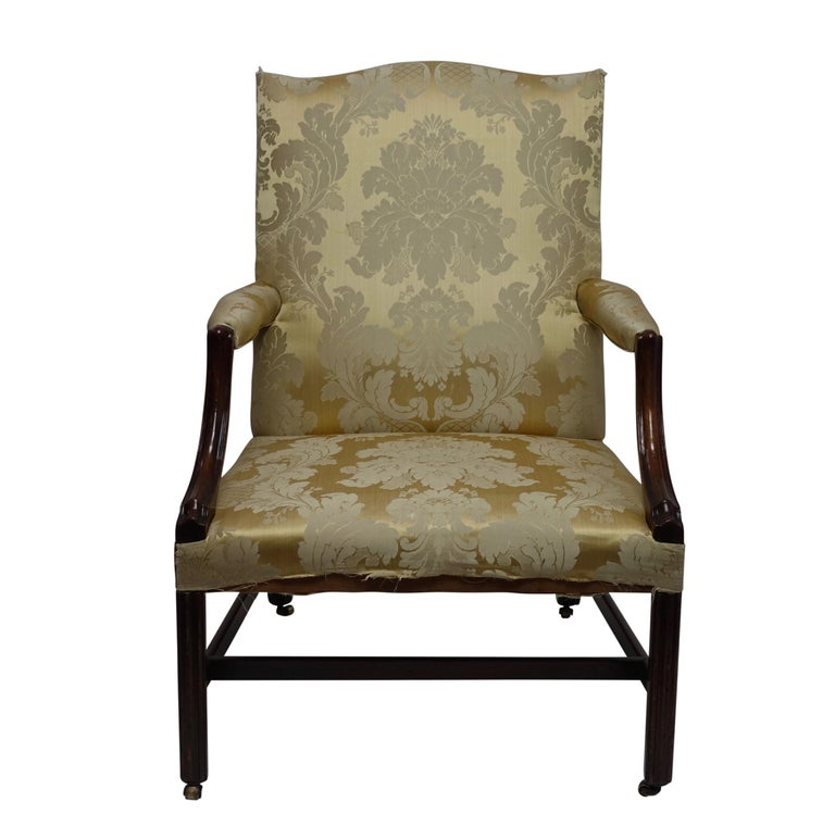 George III style Gainsborough mahogany library armchair. Having typical of the period generous proportions with carved arms, chamfered legs and original brass casters. English, Circa 1760.