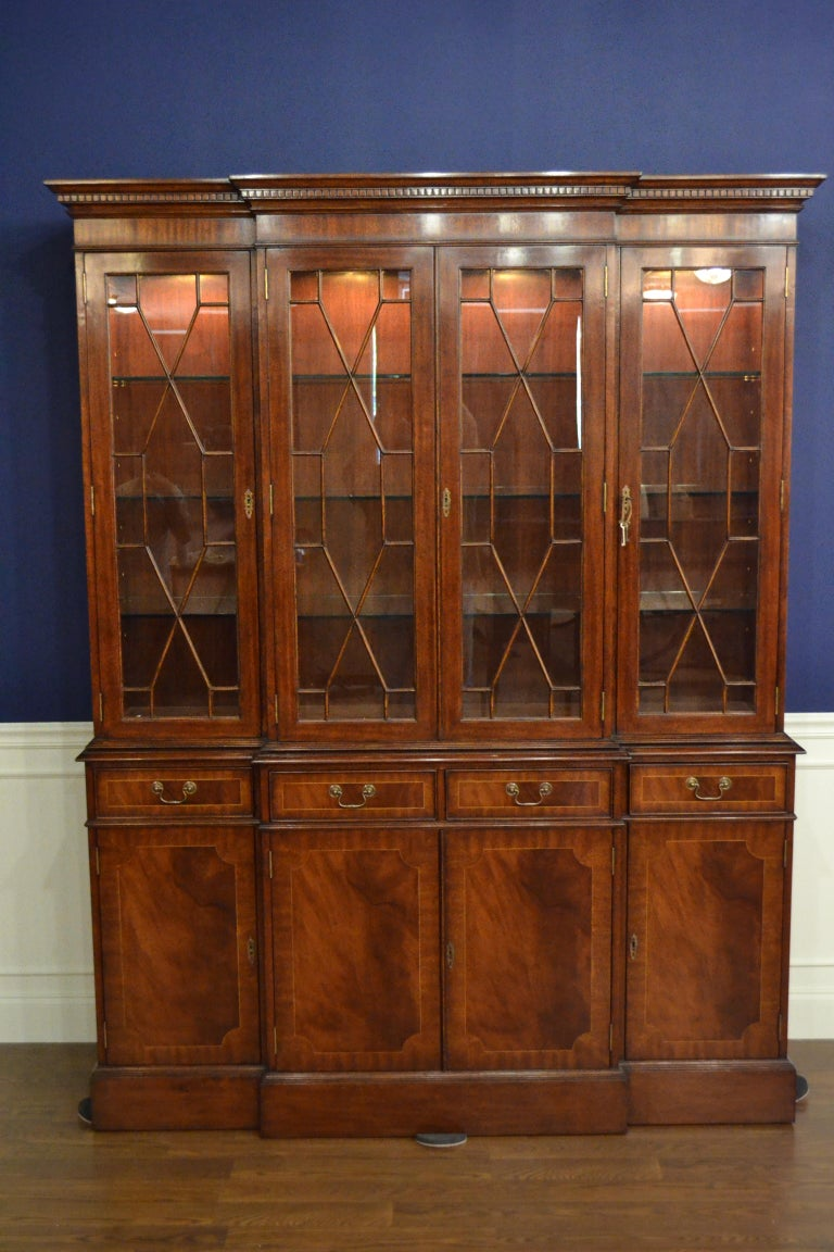 This a traditional mahogany breakfront bookcase or china cabinet with four doors by Leighton Hall. It features four bottom doors with swirly crotch mahogany fields and straight grain mahogany borders. The top four doors feature grills with