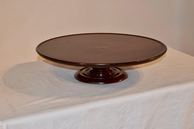 Mahogany lazy susan from England with a pie crust edge and a central inlay medallion of a fan. The base is nicely hand-turned.