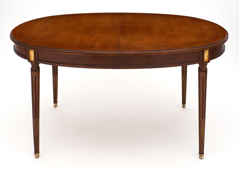 Louis XVI style antique mahogany dining table featuring an oval shape and gold leaf detail. We love the long, tapered legs and bronze feet. This table has been finished with a natural wax. The table does open for additional leaves, though we do not