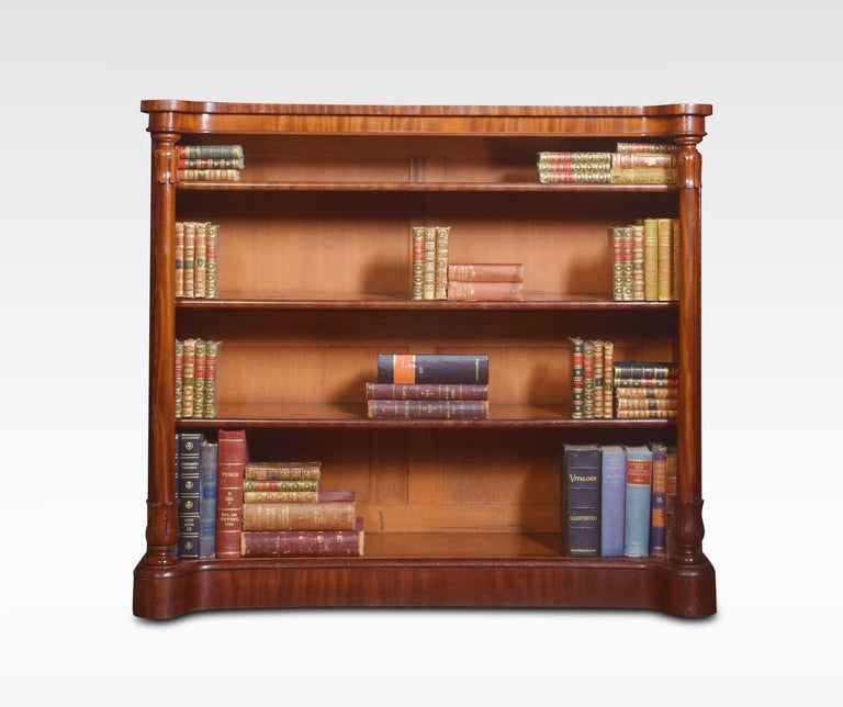 19th century mahogany bookcase, the shaped well-figured top supported on circular columns with carved capitals. Enclosing three fixed shelves, all raised up on plinth base. Dimensions Height 46 inches Width 52.5 inches Depth 19 inches.