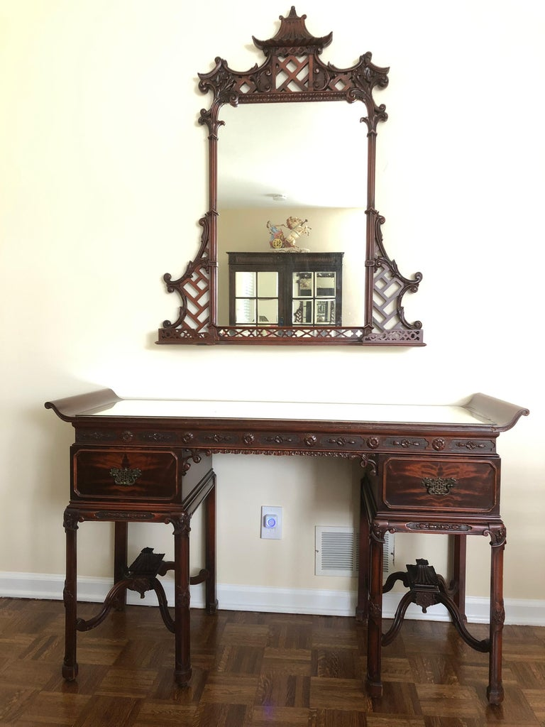 An elegant Asian style vanity or desk with matching mirror having pagoda motif. The vanity has two drawers and an authentically aged mirrored surface with fabulous stretcher and carved central pagoda underneath. The mirror can either hang above the