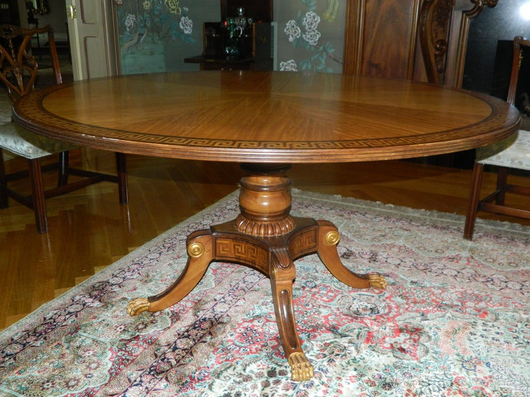 20th century mahogany round table with Greek key inlay on a decorative pedestal and gold painted paw feet.