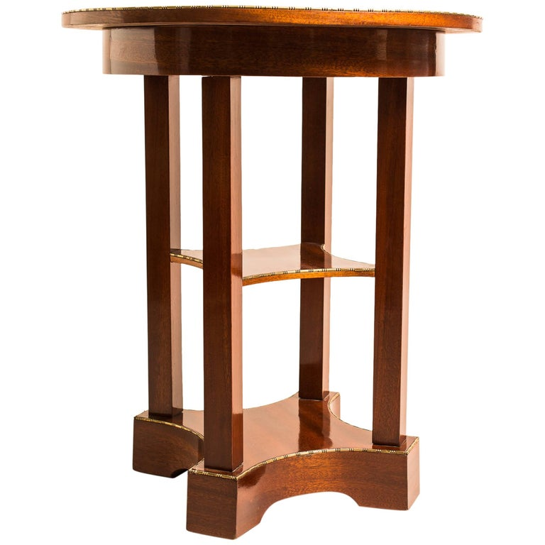Very pleasing round Austrian mahogany side table from the early 20th century, circa 1910. A valuable piece of Viennese furniture, made with finest mahogany veneer. The round top plate sits on four square columns which are mounted on a fantastic