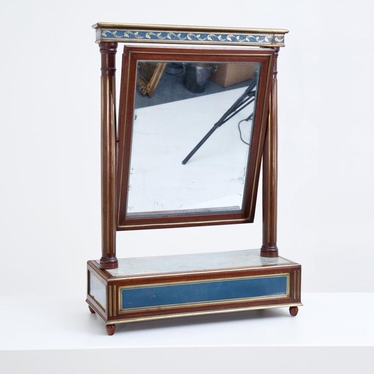Classicist table mirror in mahogany with verre églomisé inlays in blue and gold. The mirror is mounted between fluted columns with straight architrave and pivots.