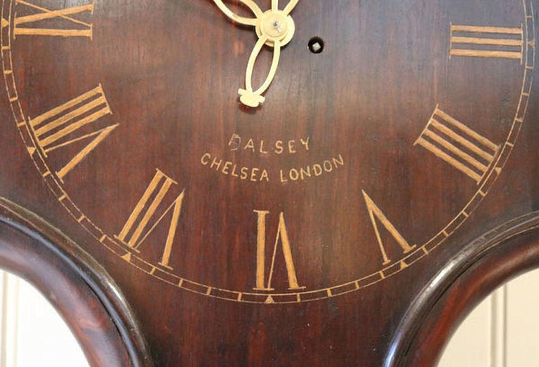 A solid mahogany English Tavern clock, made at the beginning of the 20th century, with a period fusee movement. The 18th century styled case has a shaped and pegged dial with gilt numeral and brass hands and is named Dalsey, Chelsea. It has an 8 day