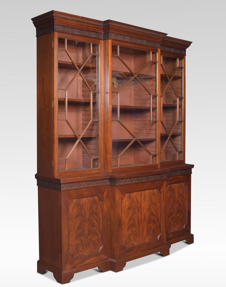 Large Chippendale revival mahogany bookcase the carved moulded blind fret projecting cornice, above one large central astragal glazed door flanked by two further small glazed doors opening to reveal an adjustable shelved interior. To the base